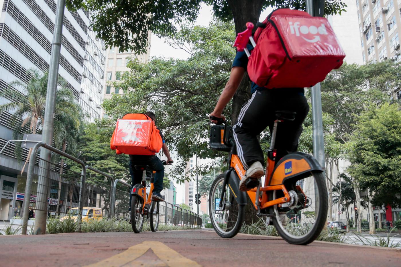 entregadores de aplicativo em cima de bicicletas laranjas do Itaú