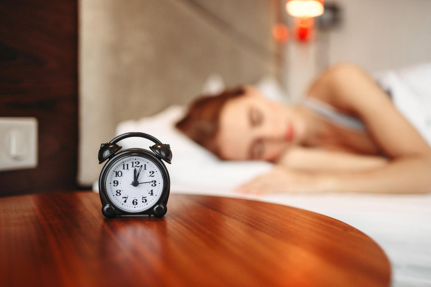mulher dormindo com relógio em primeiro plano