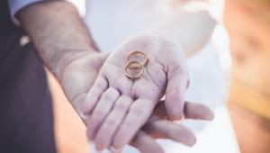 Noivos mostram as mãos segurando aliança