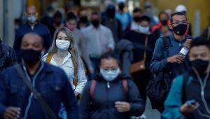 Pessoas de máscara andando na rua