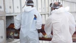 Pessoas de roupa branca colocando caixão em mausoléu