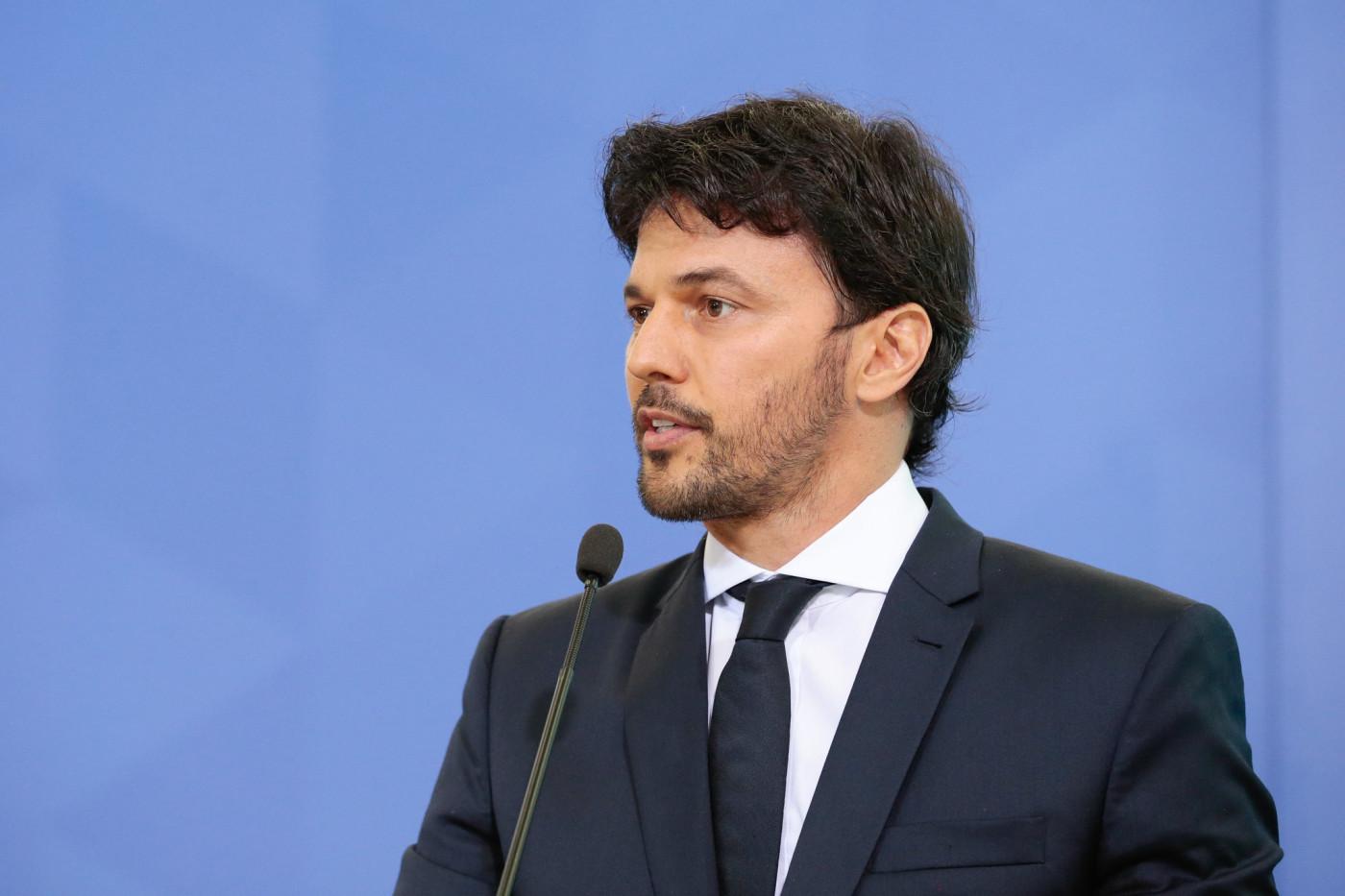 O ministro das Comunicações Fábio Faria olhando para o lado e usando terno preto