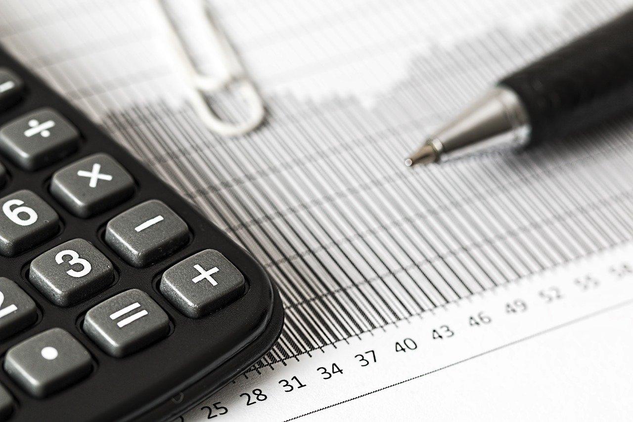 Imagem mostra uma calculadora, uma canela e papéis para planilhas de acompanhamento financeiro