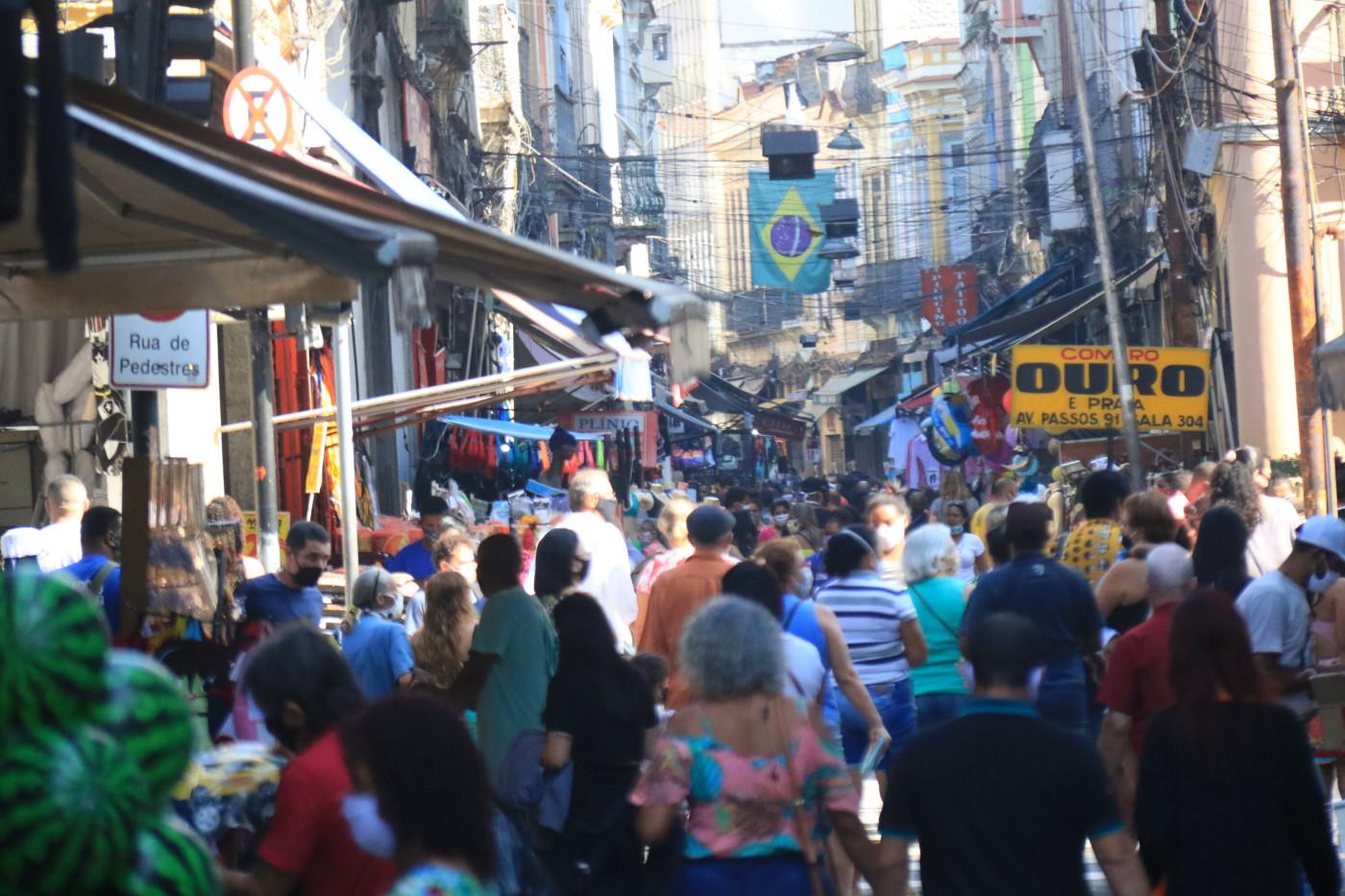 Pessoas caminhando em uma rua cheia com uma bandeira do Brasil atrás