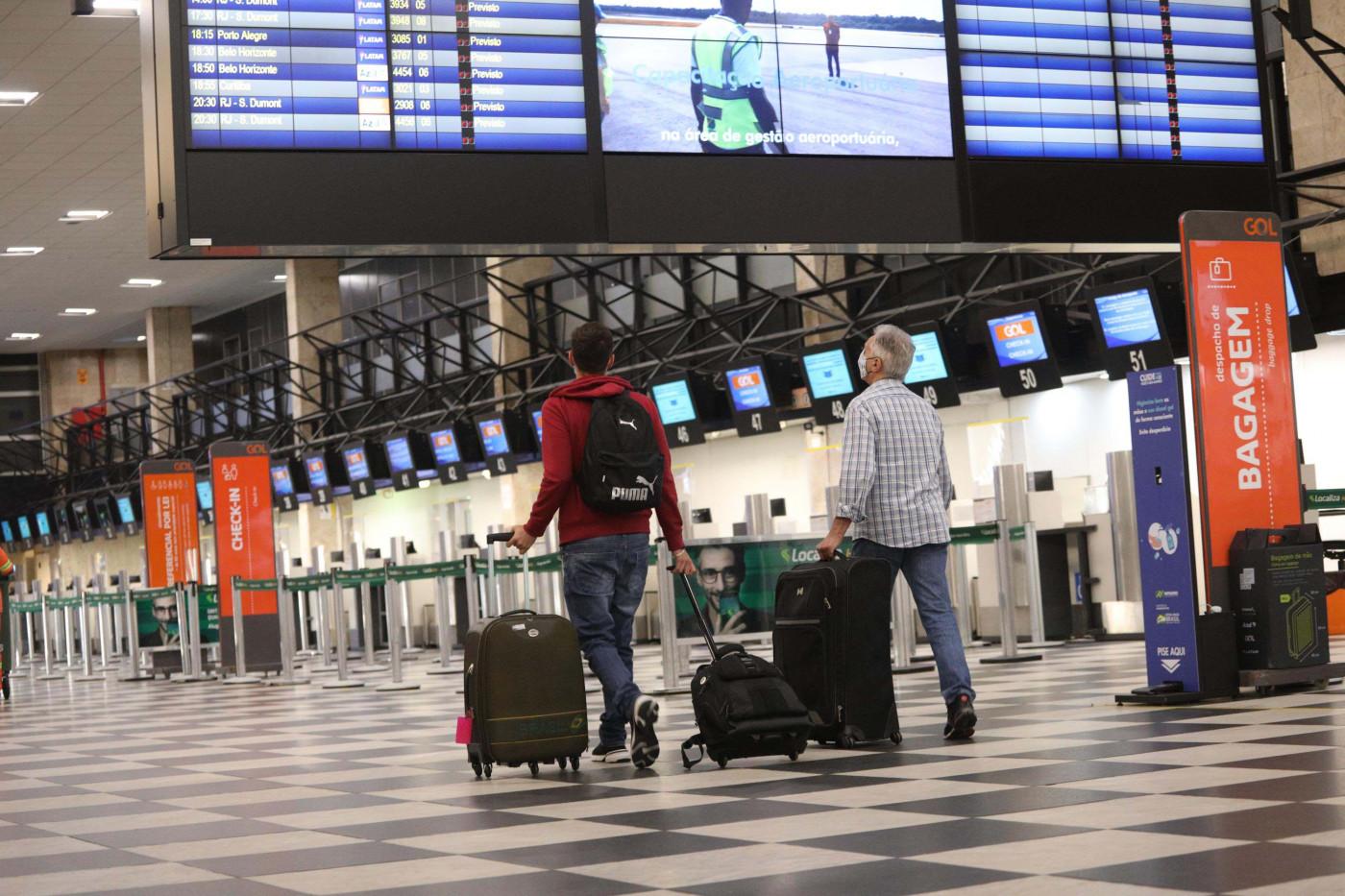 Passageiros andam dentro de aeroporto vazio