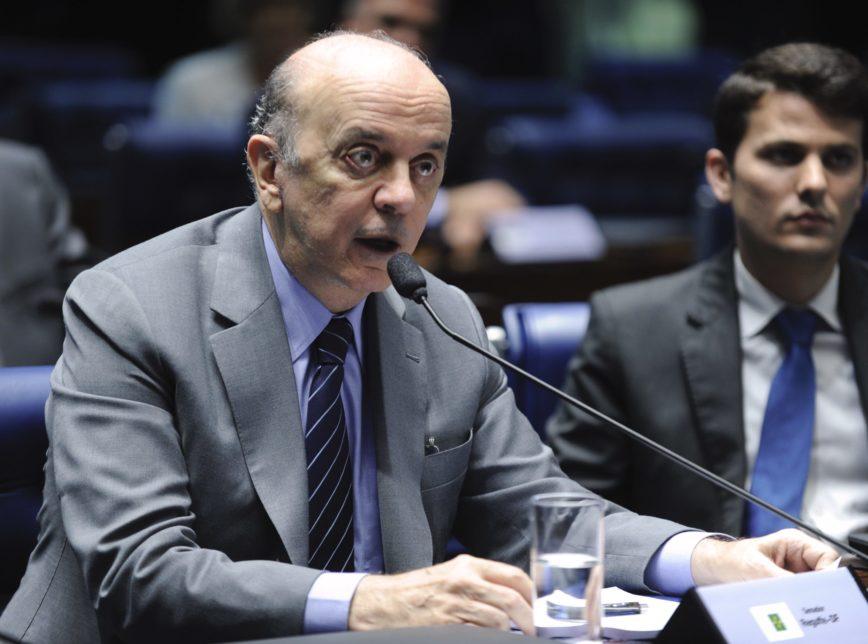 José serra, homem idoso careca, falando ao microfone em sessão do Senado. Ele usa um terno cinza, uma camisa azul e uma gravata preta listrada