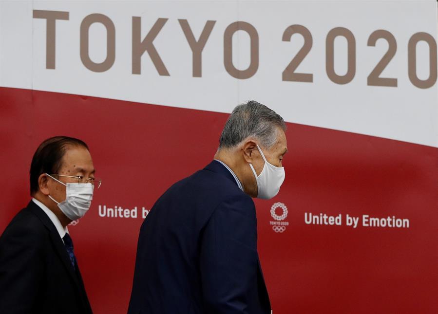 Duas pessoas caminhando de máscaras em frente a um painel escrito Tokyo 2020