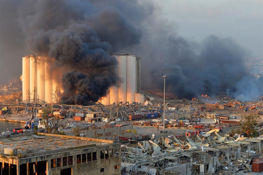 Foto aérea que mostra várias casas de cor clarano Líbano e uma densa fumaça preta saindo ao fundo de um prédio
