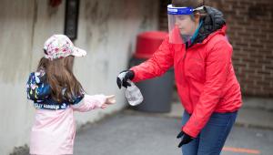 Mulher coloca álcool gel na mão de uma menina