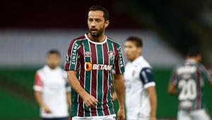 O meia Nenê , com a camisa tricolor do Fluminense, durante partida contra o Cerro Porteño; dois adversários aparecem ao fundo, desfocados