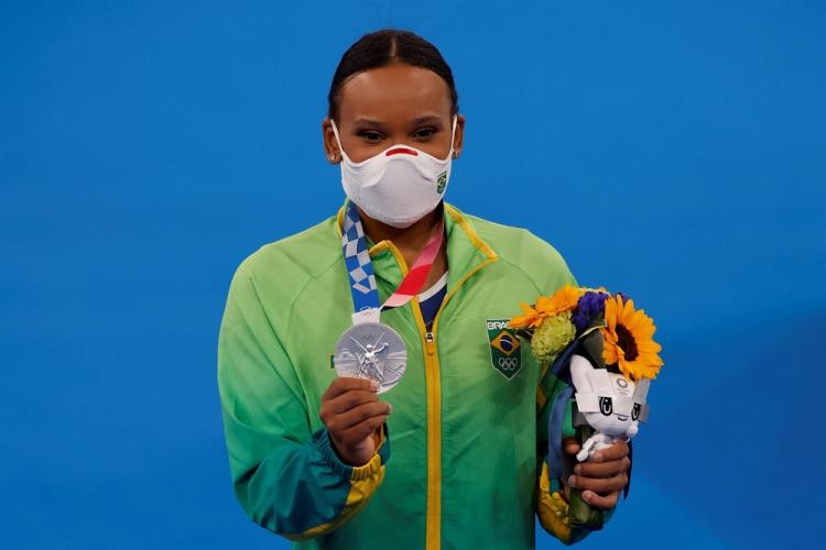 Usando máscara e o uniforme verde da delegação brasileira, Rebeca Andrade segura o mascote dos Jogos e um buquê de flores na mão esquerda e a medalha, e a medalha com a mão direita