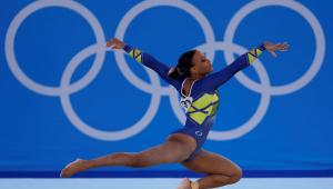 Com o joelho esquerdo flexionado e a perna direita estendida para trás, Rebeca Andrade faz sua apresentação no solo