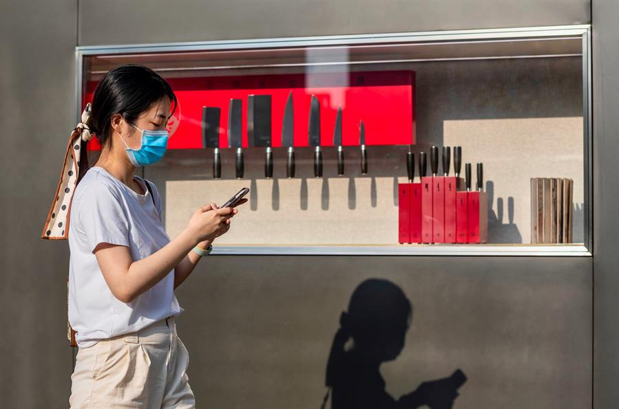 Mulher de máscara anda mexendo no celular na China