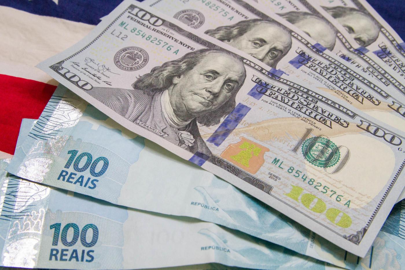 Notas de real e dólar espalhadas em cima de uma bandeira dos Estados Unidos
