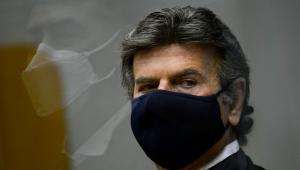 presidente do supremo, luiz fux, de máscara preta. ele é um homem branco, de cabelo grisalho. a foto mostra somente o rosto olhando para o lado