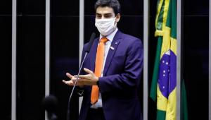 Deputado tiago Mitraud falando no microfone em sessão na Câmara de máscara e terno azul escuro, com gravata laranja.