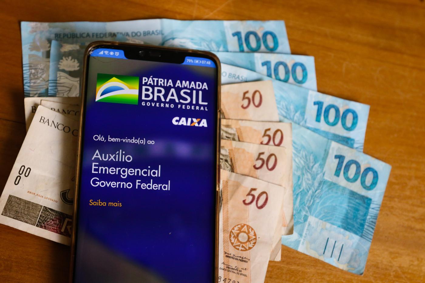 Um celular logado no aplicativo da Caixa para o recebimento do auxílio emergencial e notas de dinheiro ao lado do aparelho