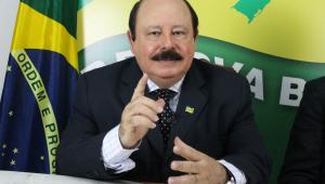 Homem discursa com bandeira do Brasil ao fundo