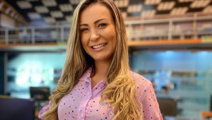Andressa Urach sorrindo e olhando para a câmera com um vestido de mangas compridas rosa. Ela tem o cabelo liso, comprido e loiro e a pele bronzeada