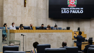 Grupo de vereadores reunidos em um saguão com a imagem da prefeitura de são paulo na direita e uma cruz pendurada na parede à esquerda