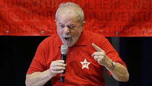 Homem de camisa vermelha com estrela do PT, cabelos grisalhos, apontando dedo e gritando