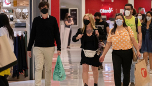 pessoas caminhando dentro de um lugar usando máscaras