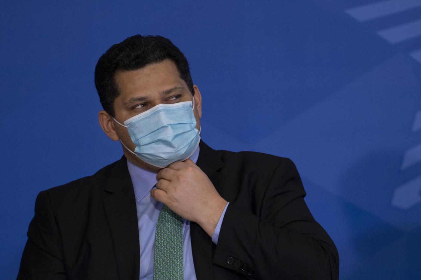De máscara, o senador Davi Alcolumbre ajeita a gravata e olha para a sua esquerda