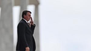 presidente Jair Bolsonaro de lado com a mão sobre o rosto