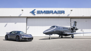 Um carro e um avião na frente de um armazém da Embraer