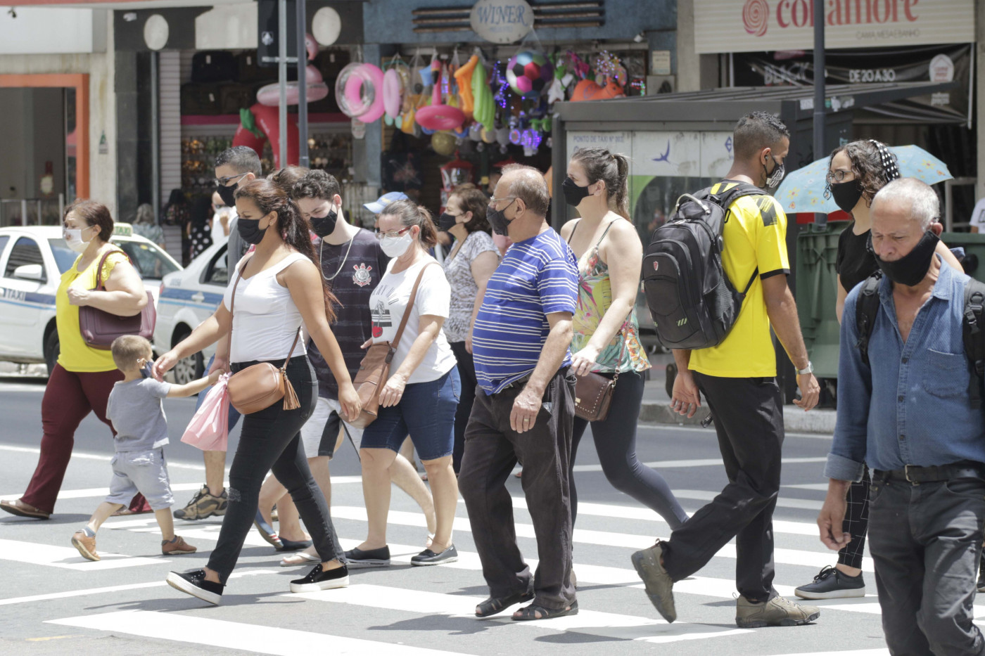 Pessoas caminhando de máscara pelo centro de uma cidade