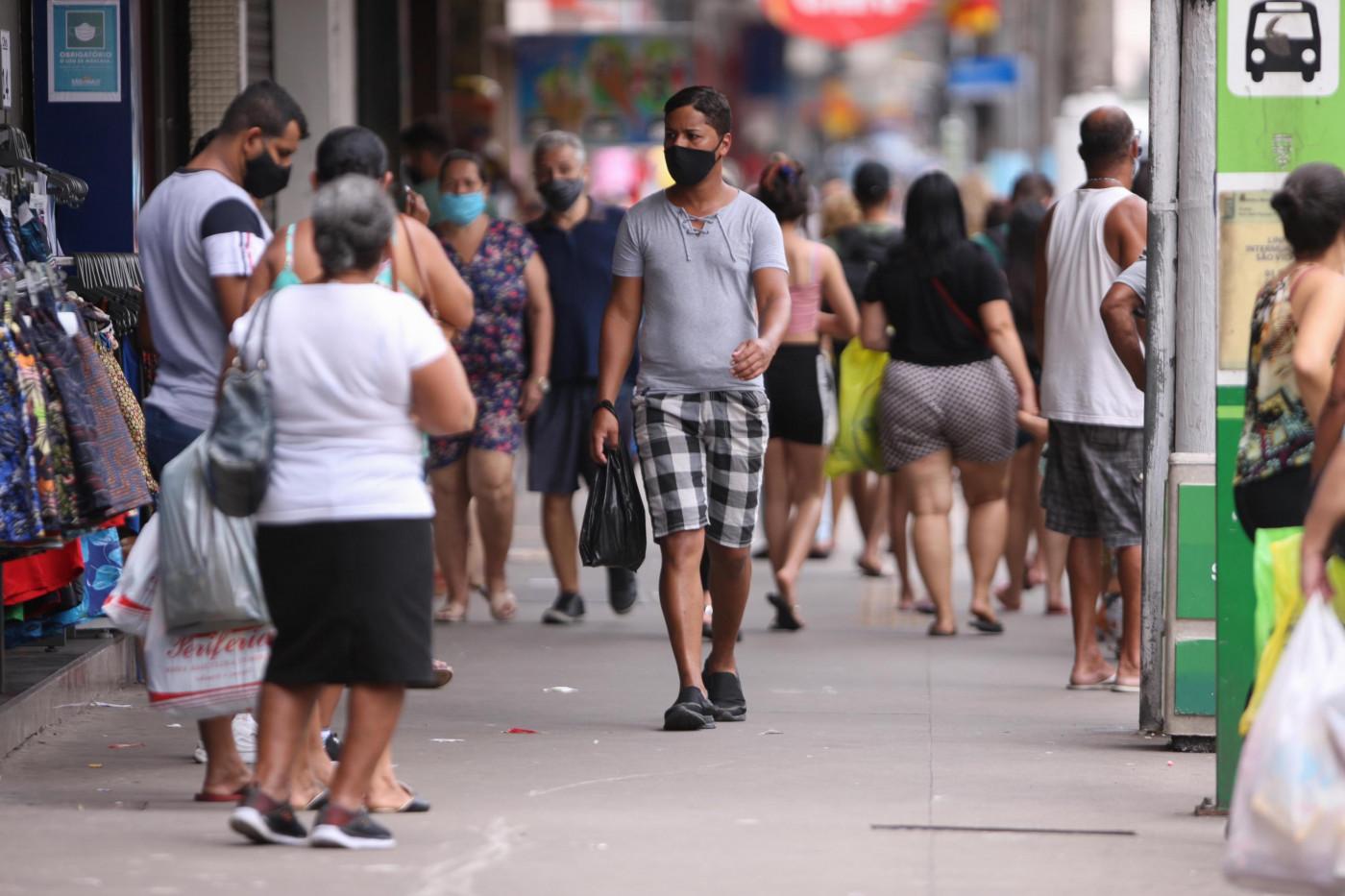 Pessoas andando na rua de máscara em Santos