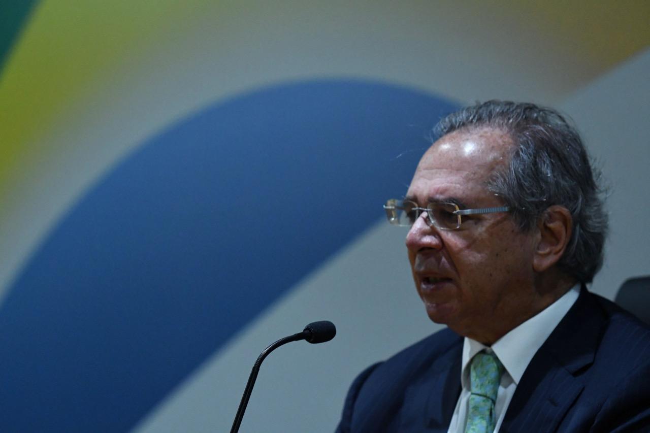 Homem calvo de cabelo grisalho e óculos com armação fina fala em microfone diante da bandeira do Brasil