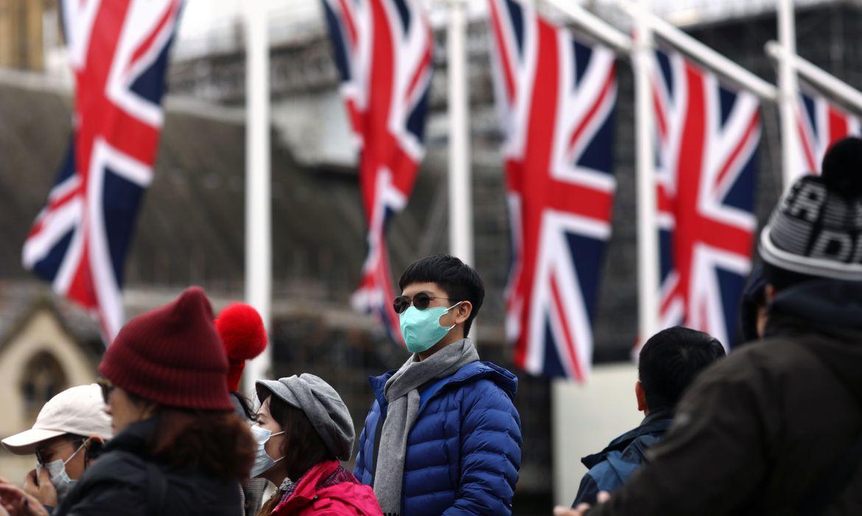 Homem com máscara de proteção em local público do Reino Unido