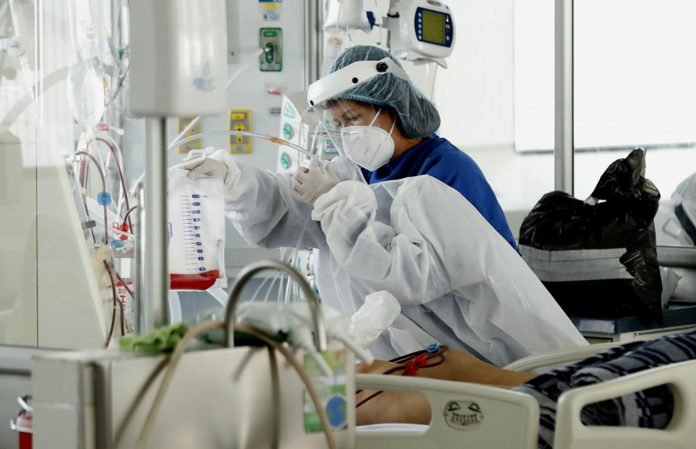 Profissional da saúde cuida de paciente internado com Covid-19