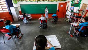 crianças sentadas em carteiras com distanciamento em uma escola. uma professora está no meio, com um quadro verde atrás.