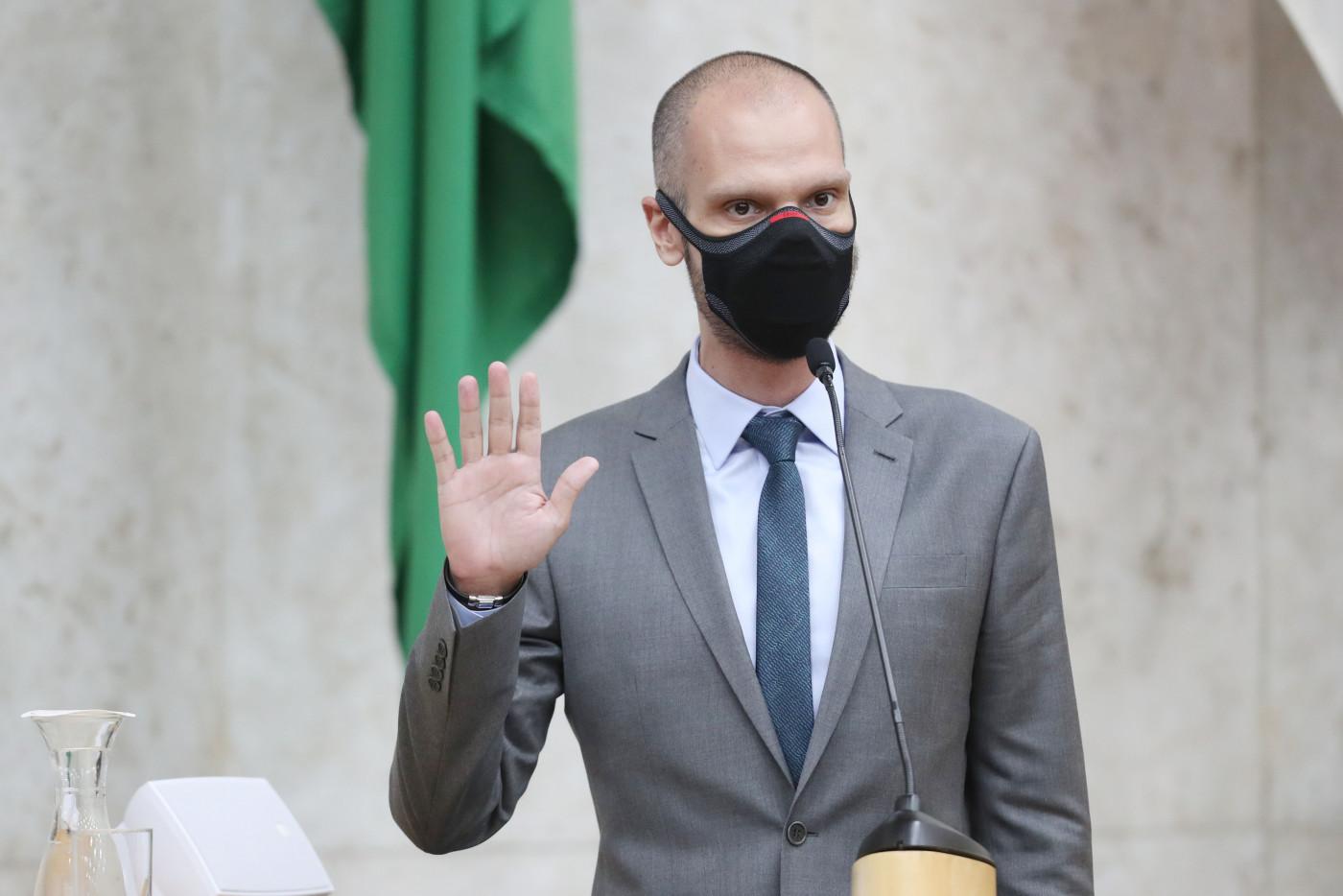 Homem careca usando máscara preta de terno cinza e gravata azul