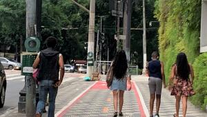 Pedestres andam sobre faixa destinada a ciclistas em uma calçada no centro de São Paulo
