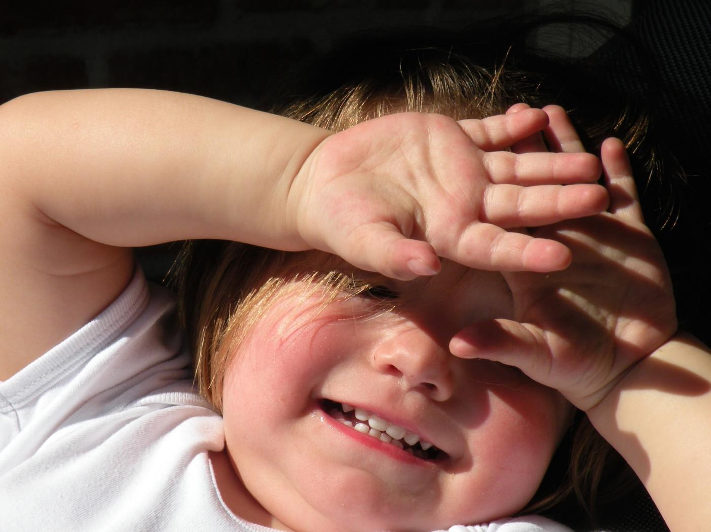 criança cobrindo olho