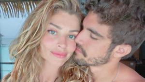 Caio castro beijando o rosto de Grazi Massafera. A atriz está olhando para a foto e ele olha para ela