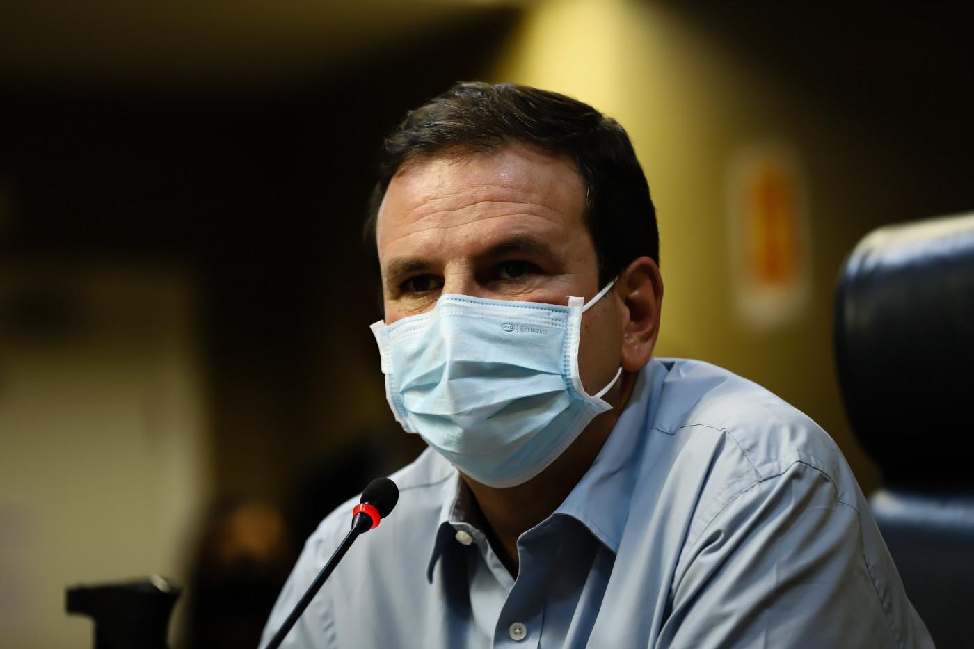 Homem de máscara azul e camisa azul falando em microfone