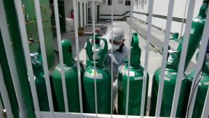 vários cilindros de oxigenio verdes, um sendo manuseado por um profissional da saúde. grade branca em primeiro plano na foto