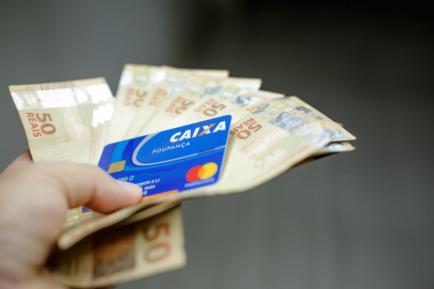 várias notas de 50 reais em uma mão junto com um cartão azul da caixa