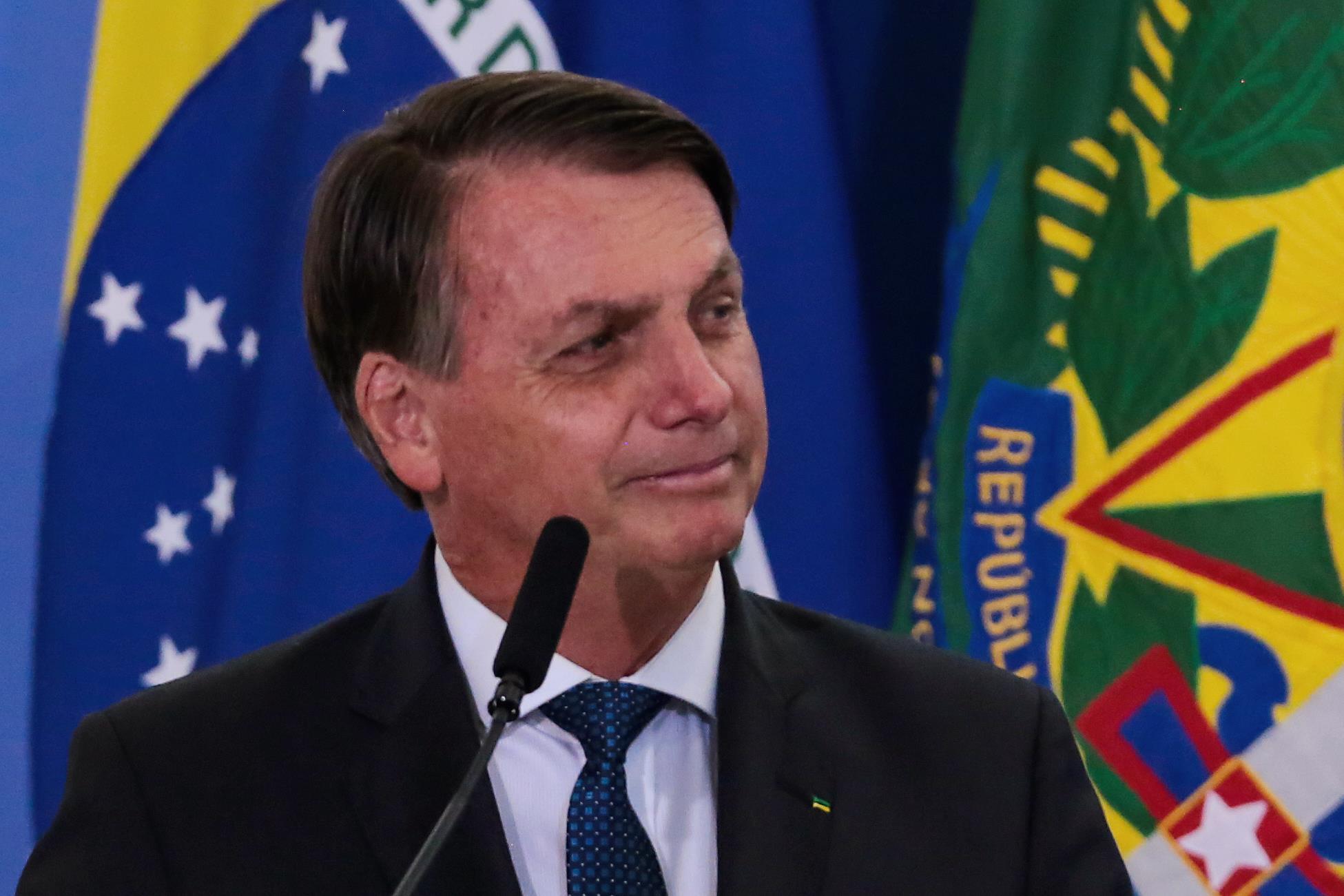 jair bolsonaro olhando para o lado de terno, atrás de um microfone e na frente de uma bandeira do brasil