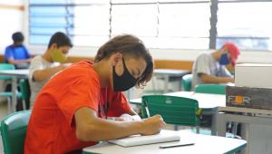 Criança escreve em caderno