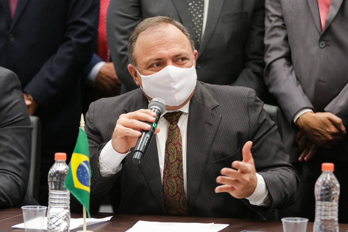 Homem de terno preto e gravata marrom usando máscara branca sentado diante de uma mesa com duas fileiras de papéis brancos, uma miniatura da bandeira do Brasil e duas garrafas de água; ele gesticula com a mão esquerda e segura um microfone com a mão direita