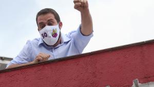 Homem de cabelo preto trajando máscara branca com o número 50, uma camisa azul de botão e de punho levantado diante de um céu azul