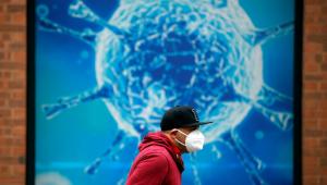 homem andando de máscara com um painel simulando o coronavírus no fundo