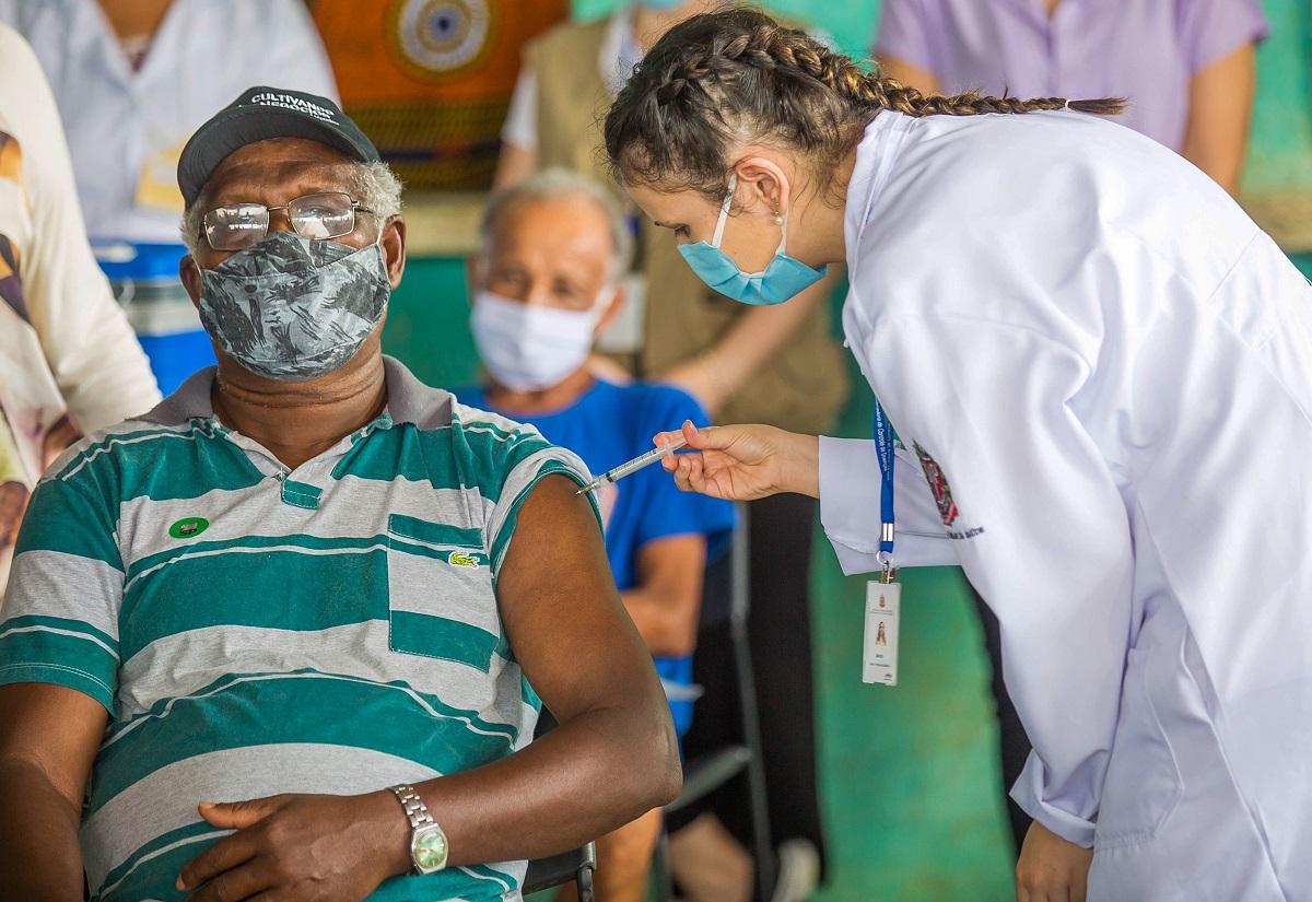 Homem de máscara recebendo vacina no braço