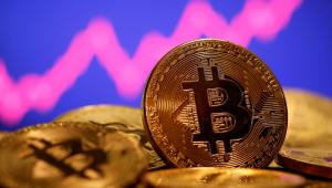 Moedas de bitcoin com gráfico rosa e fundo azul atrás
