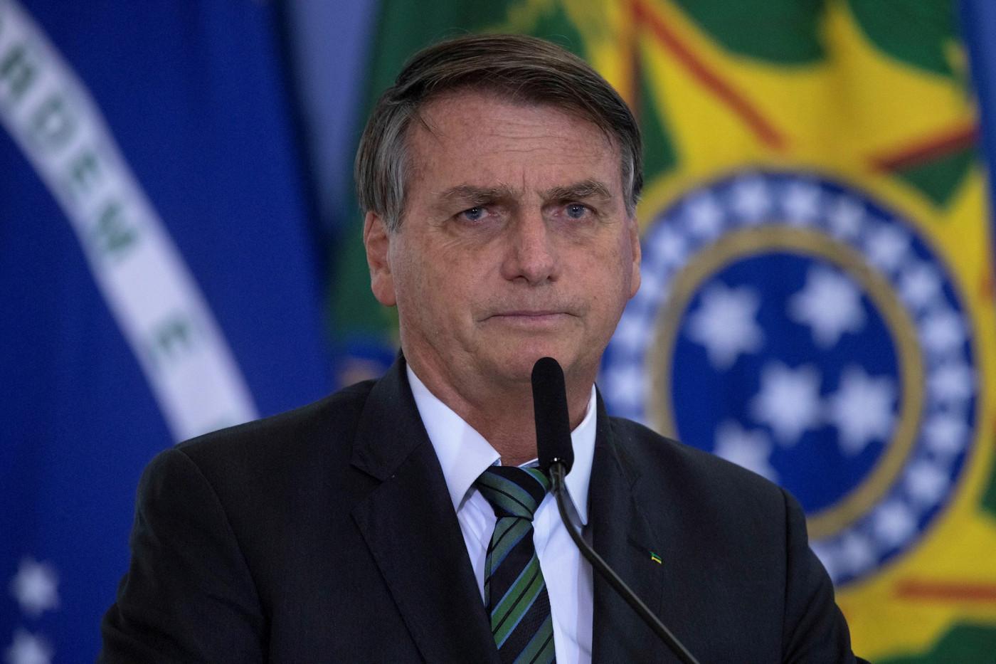 Homem de cabelo grisalho trajando terno e gravata pretos falando em microfone diante de uma bandeira do Brasil